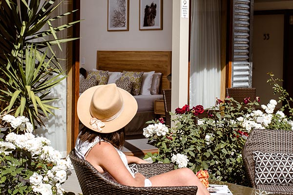A lady sits outside in a straw hat surrounded by roses, looking inside to her boutique hotel room