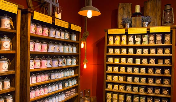 A dim-lit room, lined with large shelves stacked with colourful candles