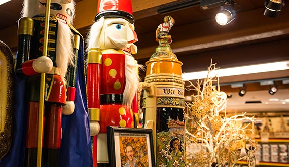 A selection of German nutcrackers and steins in a room with rustic wooden pillars