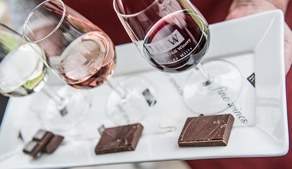 Three glasses of wine displayed upon a white platter with three chocolates paired