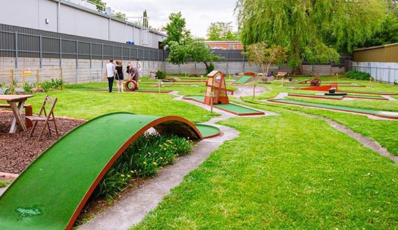 A mini golf course surrounded by lush green grass