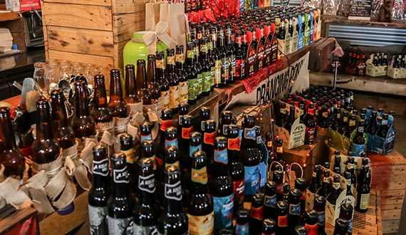 A variety of bottled beers with different coloured labels displayed upon wooden crates