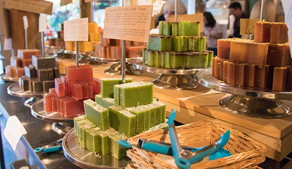 A variety of colourful soaps displayed on a wooden bench