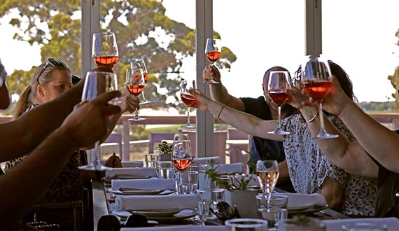 A number of diners hold their glasses of wine in the air, cheering each other