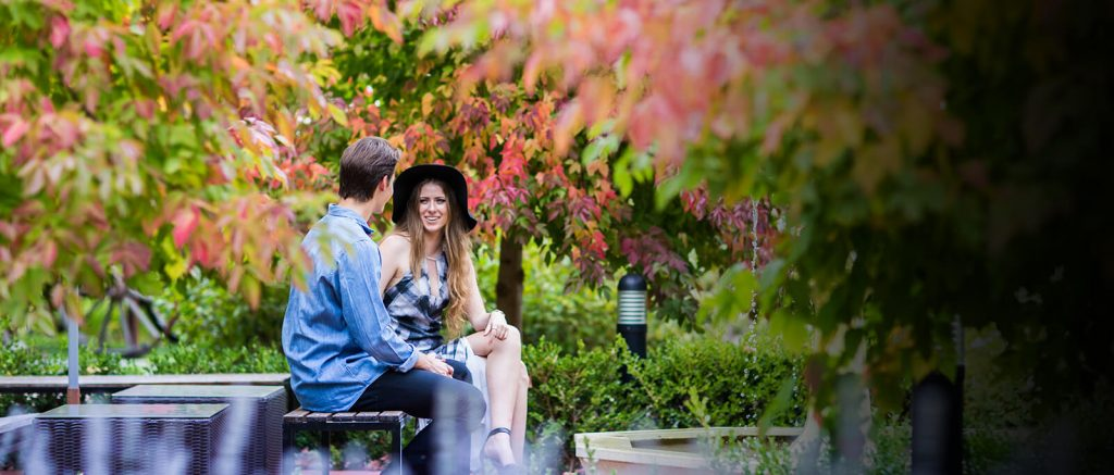 A couple sit in a colourful garden setting